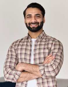 smiling bearded man with arms folded